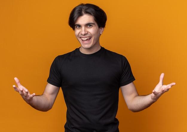오렌지 벽에 고립 된 손을 확산 검은 티셔츠를 입고 웃는 젊은 잘 생긴 남자