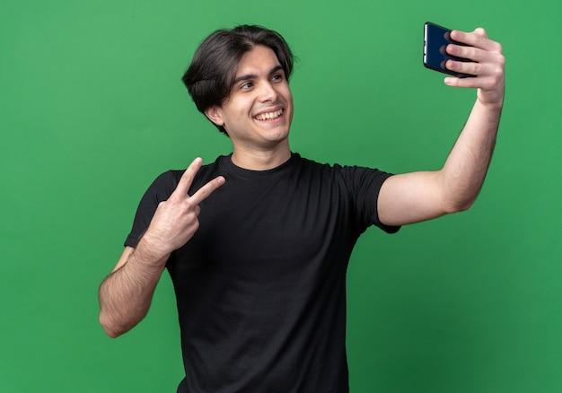 Улыбающийся молодой красивый парень в черной футболке делает селфи, показывающий жест мира, изолированный на зеленой стене