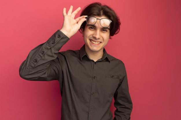 ピンクの壁に分離された眼鏡をかけて黒のtシャツを着て笑顔の若いハンサムな男