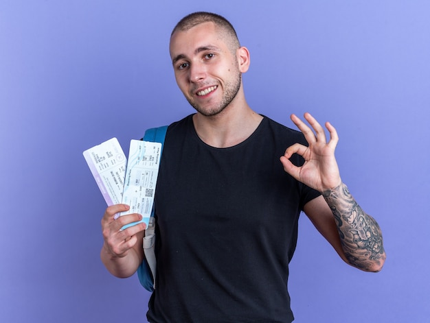 Smiling young handsome guy wearing black t-shirt with backpack holding tickets showing okay gesture isolated on blue background