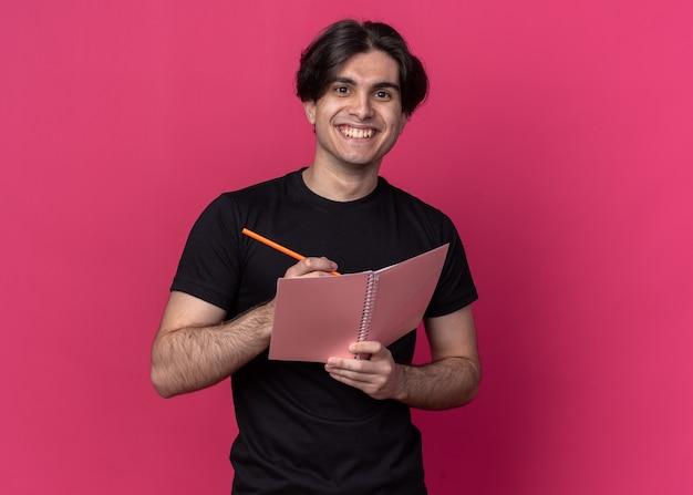 분홍색 벽에 고립 된 노트북에 뭔가 쓰는 검은 티셔츠를 입고 웃는 젊은 잘 생긴 남자