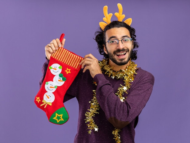 Smiling young handsome guy wearing christmas hair hoop with garland on neck holding christmas socks isolated on blue background