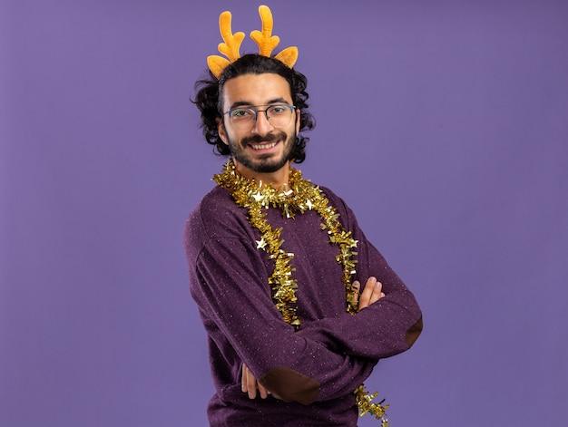コピースペースと青い背景で隔離の首の交差する手に花輪とクリスマスの髪のフープを身に着けている若いハンサムな男の笑顔