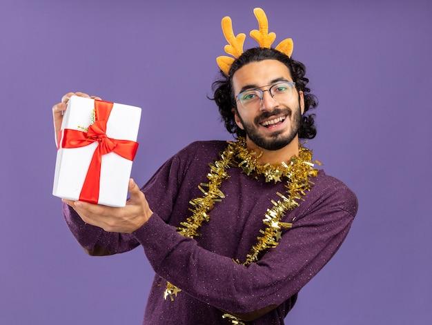 青い背景で隔離のギフトボックスを保持している首に花輪とクリスマスの髪のフープを身に着けている若いハンサムな男の笑顔