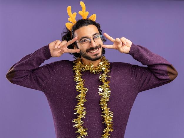 青い背景で隔離の平和のジェスチャーを示す首に花輪とクリスマスの髪のフープを身に着けている若いハンサムな男の笑顔