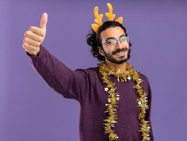 青い背景で隔離の親指を示す首に花輪とクリスマスの髪のフープを身に着けている若いハンサムな男の笑顔