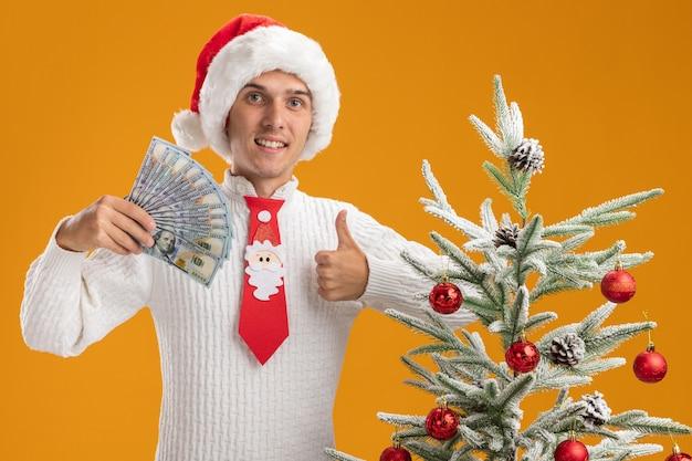 Улыбающийся молодой красивый парень в новогодней шапке и галстуке санта-клауса стоит возле украшенной елки с деньгами и смотрит вверх, показывая большой палец на оранжевой стене
