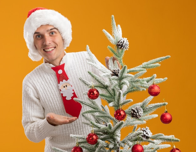 Smiling young handsome guy wearing christmas hat and santa claus tie standing behind decorated christmas tree looking  pointing with hand at christmas tree isolated on orange wall