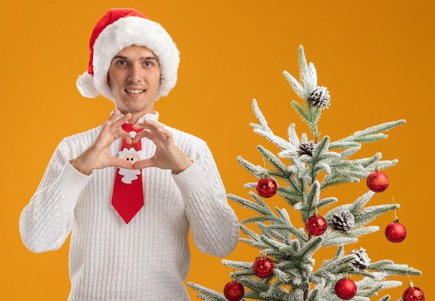Smiling young handsome guy wearing christmas hat and santa claus tie standing near decorated christmas tree looking at camera doing heart sign isolated on orange background