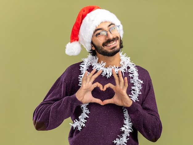 Smiling young handsome guy wearing christmas hat with garland on neck showing heart gesture isolated on olive green background