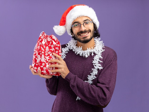 青い背景で隔離のクリスマスバッグを保持している首に花輪とクリスマス帽子をかぶって若いハンサムな男
