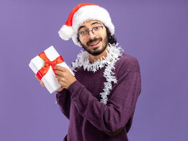 青い壁に分離されたギフト ボックスを保持している首にガーランドとクリスマスの帽子をかぶった若いハンサムな男の笑みを浮かべてください。