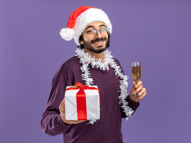 青い背景で隔離のシャンパングラスとギフトボックスを保持している首に花輪とクリスマスの帽子をかぶって若いハンサムな男