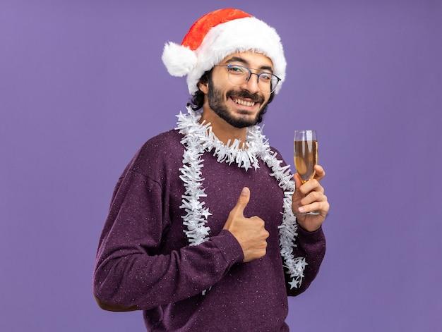 青い背景で隔離の親指を示すシャンパンのガラスを保持している首に花輪とクリスマスの帽子をかぶって笑顔の若いハンサムな男