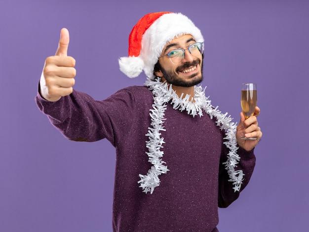 파란색 벽에 격리 엄지 손가락을 보여주는 샴페인 잔을 들고 목에 갈 랜드와 함께 크리스마스 모자를 쓰고 웃는 젊은 잘 생긴 남자