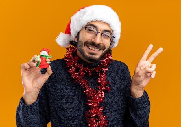 オレンジ色の壁に分離された平和のジェスチャーを示すおもちゃを持って首に花輪とクリスマスの帽子をかぶった笑顔の若いハンサムな男