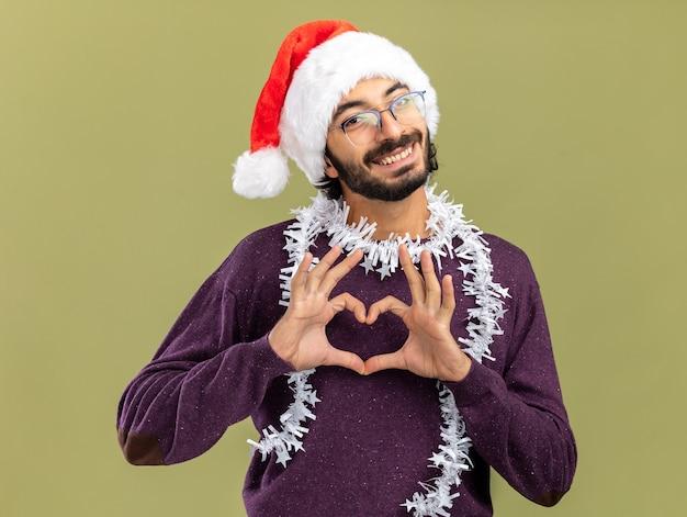 Улыбающийся молодой красивый парень в новогодней шапке с гирляндой на шее, показывая жест сердца, изолированный на оливково-зеленом фоне
