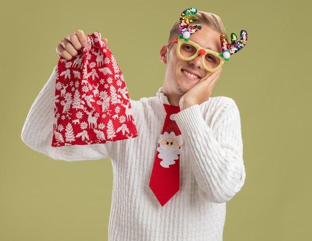 クリスマスノベルティメガネとサンタクロースのネクタイを身に着けている笑顔の若いハンサムな男は、オリーブグリーンの背景で隔離の顔に手を保ちながらカメラを見てクリスマス袋を保持しています