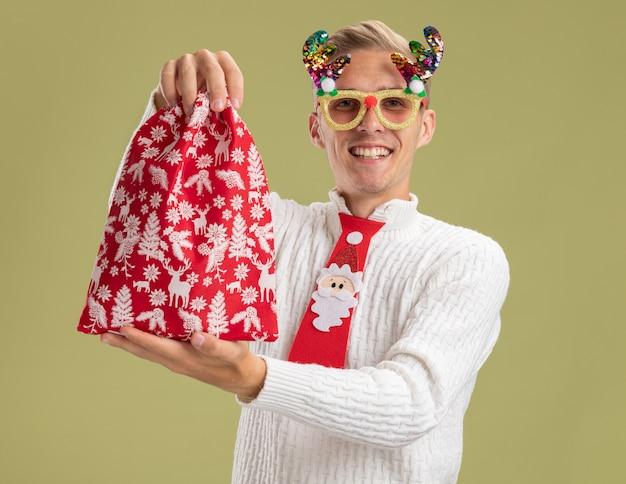クリスマスノベルティメガネとサンタクロースのネクタイを身に着けている若いハンサムな男の笑顔は、オリーブグリーンの背景で隔離のカメラを見てカメラに向かってクリスマス袋を伸ばしています。