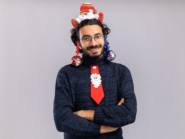Smiling young handsome guy wearing christmas tie with hair hoop hung christmas ball on ears crossing hands isolated on white wall