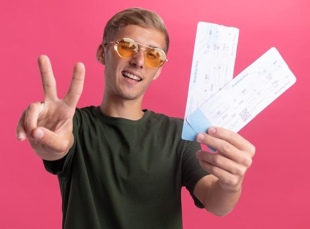 Sorridente giovane bel ragazzo indossa camicia verde e occhiali che tengono i biglietti che mostrano gesto di pace isolato sulla parete rosa