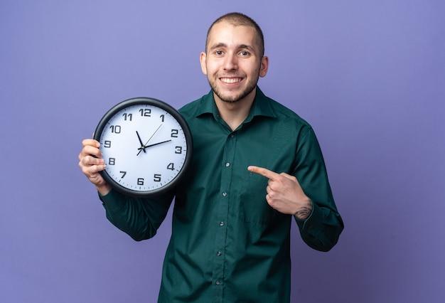 Sorridente giovane bel ragazzo che indossa una camicia verde che tiene e indica l'orologio da parete
