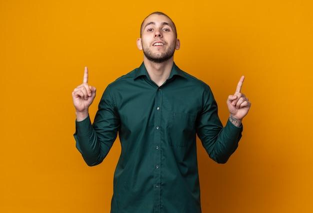 Il giovane bel ragazzo sorridente che indossa una maglietta verde punta verso l'alto