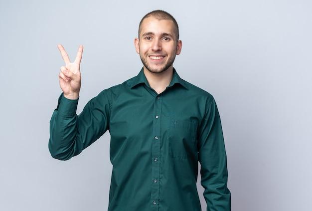 平和のジェスチャーを示す緑のシャツを着て笑顔の若いハンサムな男