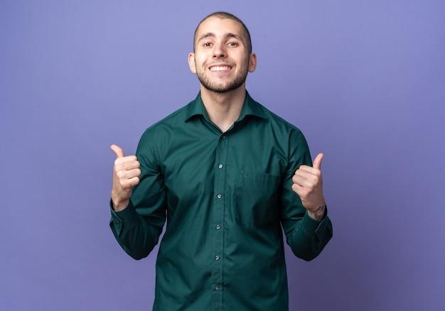Sorridente giovane bel ragazzo che indossa una camicia verde che mostra i pollici in su