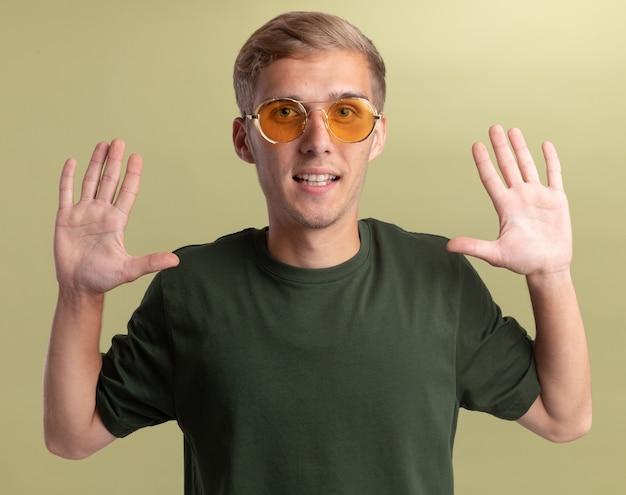 オリーブグリーンの壁に分離された手を上げる眼鏡と緑のシャツを着て笑顔の若いハンサムな男