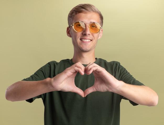 Sorridente giovane bel ragazzo indossa la camicia verde con gli occhiali che mostra il gesto del cuore isolato sulla parete verde oliva