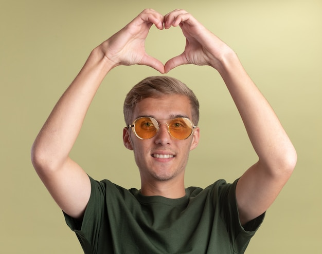 올리브 녹색 벽에 고립 된 심장 제스처를 보여주는 안경 녹색 셔츠를 입고 웃는 젊은 잘 생긴 남자