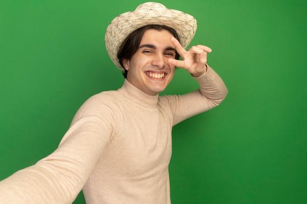 緑の壁に分離された正面を保持している平和ジェスチャーを示す帽子をかぶって笑顔の若いハンサムな男