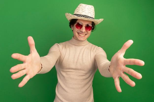 Sorridente giovane bel ragazzo che indossa il cappello con gli occhiali tendendo le mani davanti isolato sulla parete verde