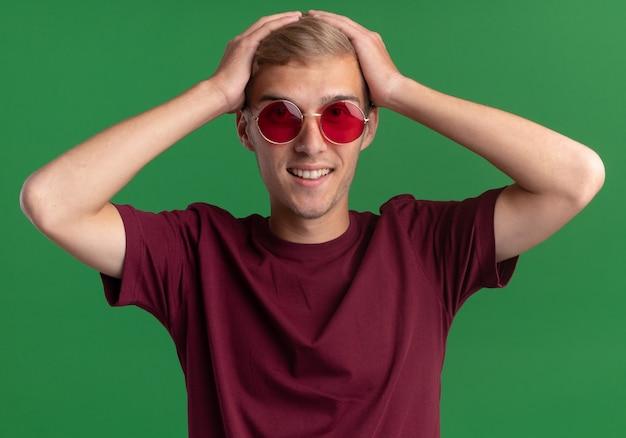 빨간 셔츠와 안경을 쓰고 웃는 젊은 잘 생긴 남자가 녹색 벽에 고립 된 머리를 잡고