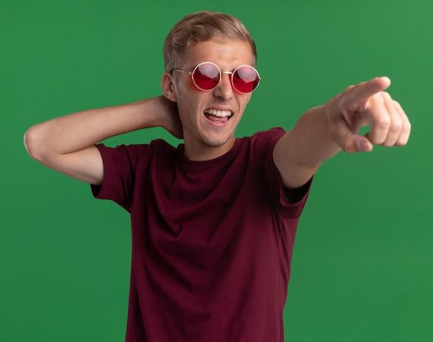 녹색 벽에 고립 된 측면에서 머리와 포인트 뒤에 손을 넣어 빨간 셔츠와 안경을 쓰고 웃는 젊은 잘 생긴 남자