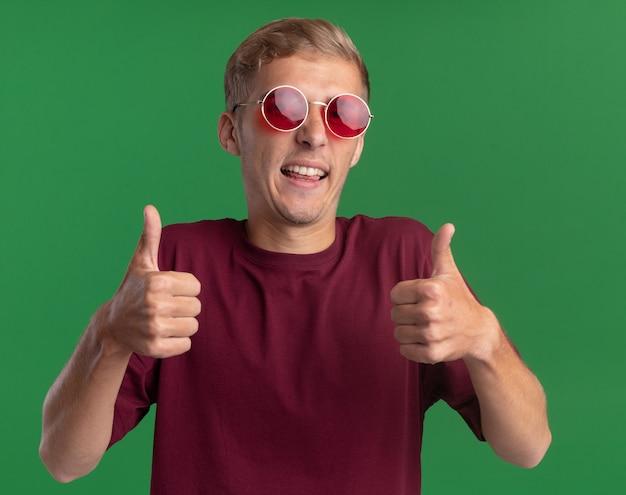 Sorridente giovane bel ragazzo indossa la camicia rossa e gli occhiali che mostrano i pollici in su isolato sulla parete verde