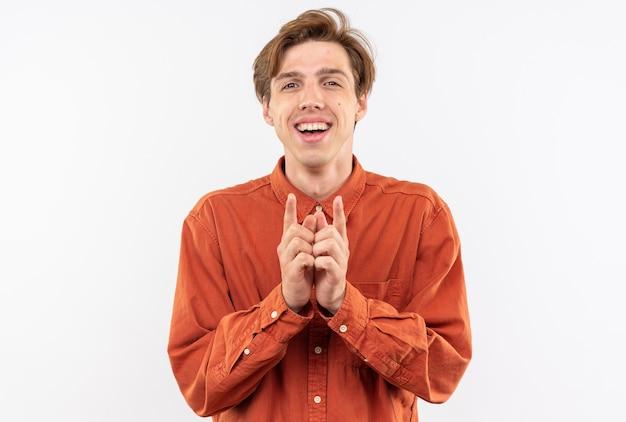 白い壁に分離された手を一緒に持って赤いシャツを着て笑顔の若いハンサムな男