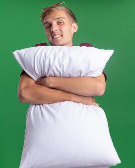 Улыбающийся молодой красивый парень в красной рубашке обнял подушку, изолированную на зеленой стене