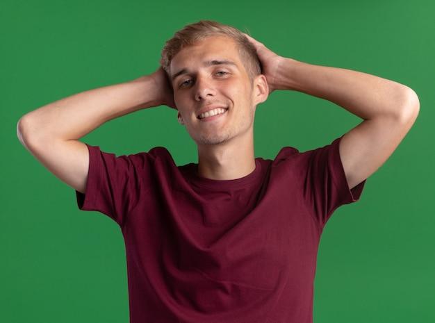 녹색 벽에 고립 된 머리 뒤에 손을 댔을 빨간 셔츠를 입고 웃는 젊은 잘 생긴 남자