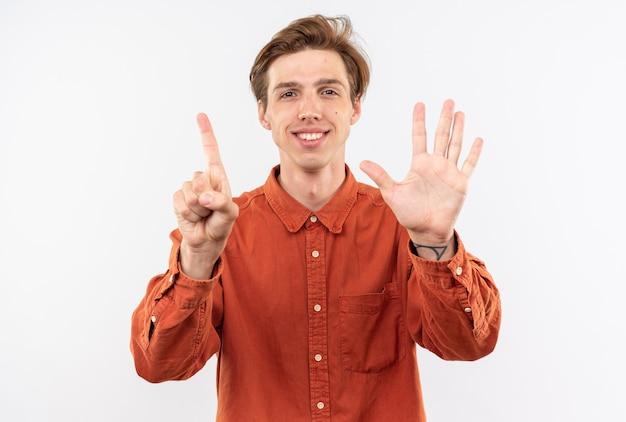 白い壁に分離された異なる番号を示す赤いシャツを着て笑顔の若いハンサムな男