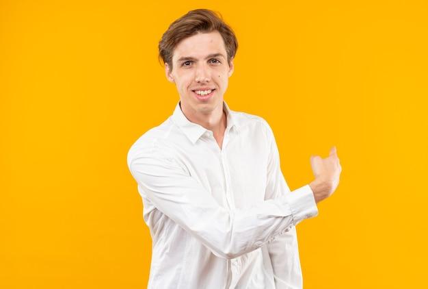 白いシャツを着て笑顔の若いハンサムな男は、コピースペースとオレンジ色の壁に分離された後ろを指しています