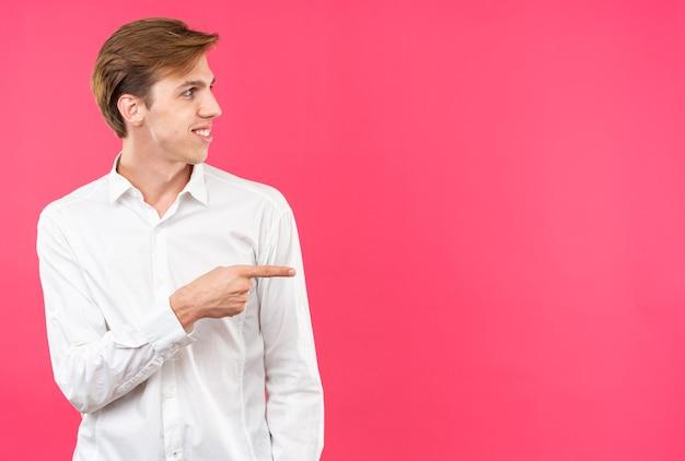 복사 공간이 있는 분홍색 벽에 격리된 쪽에 흰색 셔츠 포인트를 입은 웃고 있는 젊은 미남