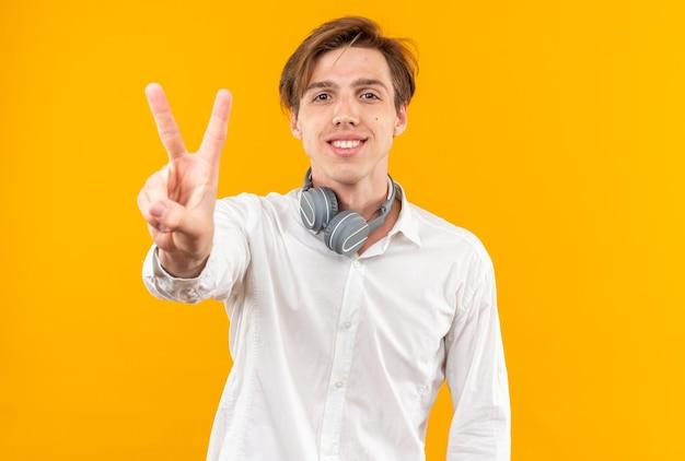 平和のジェスチャーを示す首にヘッドフォンで白いシャツを着て笑顔の若いハンサムな男