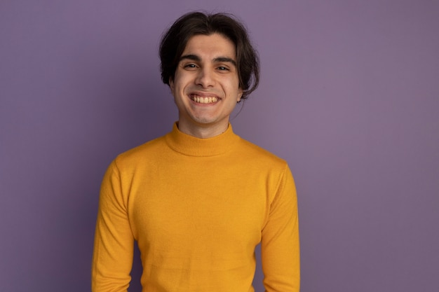 복사 공간 보라색 벽에 고립 된 노란색 터틀넥 스웨터를 입고 웃는 젊은 잘 생긴 남자