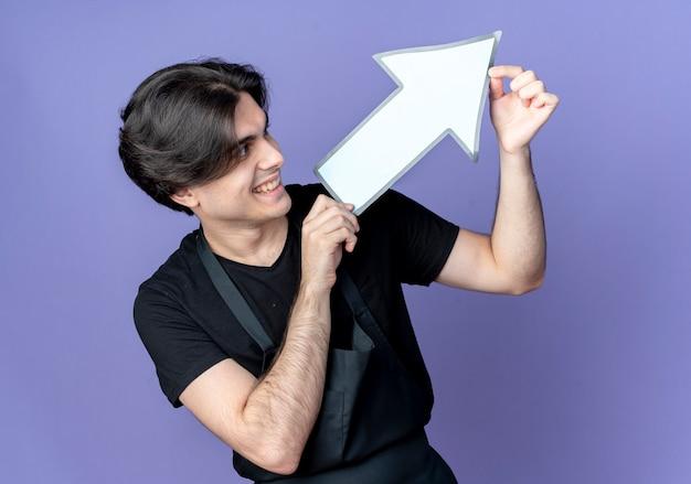 Улыбающийся молодой красивый мужчина-парикмахер в униформе, держащий и смотрящий на указатель направления бумаги, изолированный на синем