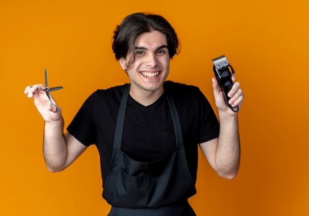 오렌지에 고립 된 머리 깎기와 가위를 들고 제복을 입은 젊은 잘 생긴 남성 이발사 미소