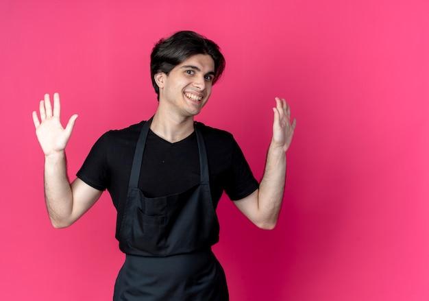 제복을 입은 젊은 잘 생긴 남성 이발사 미소는 복사 공간이 분홍색에 고립 된 손을 확산