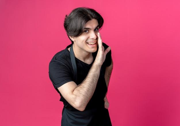 ピンクで隔離の均一なささやきで若いハンサムな男性理髪店の笑顔
