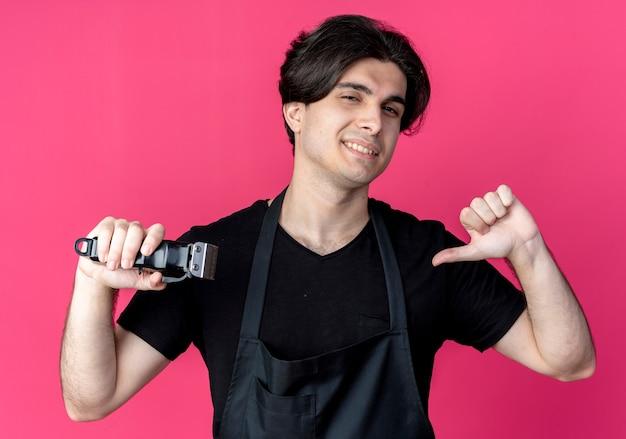 Sorridente giovane barbiere maschio bello in uniforme che tiene tagliacapelli e punti se stesso isolato sul rosa